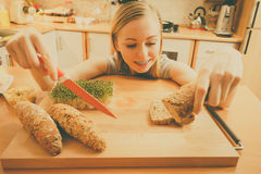 Woman in kitchen holding knife making healthy sandwich Stock Images