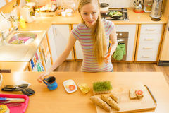 Woman in kitchen holding knife making healthy sandwich Royalty Free Stock Photos