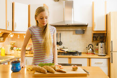 Woman in kitchen holding knife making healthy sandwich Stock Photos