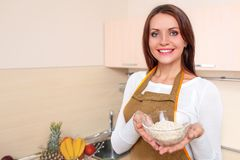 Woman at kitchen holding plate of oatmeal Stock Image