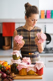 Woman in kitchen holding preserves and looking at jars Stock Images
