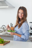 Woman in the kitchen holding a salad bowl Stock Photos