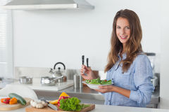 Woman in the kitchen holding a salad bowl with lettuce Stock Photos