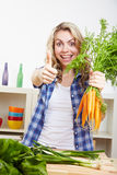 Woman in kitchen holding thumbs up Stock Photos