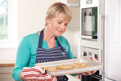 Woman In Kitchen Holding Tray With Home Baked Cookies Royalty Free Stock Photography