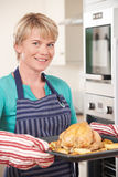 Woman In Kitchen Holding Tray With Roast Chicken Stock Photo