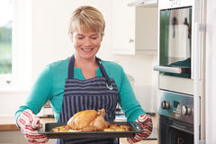 Woman In Kitchen Holding Tray With Roast Chicken Royalty Free Stock Photography