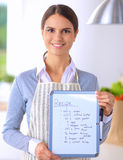 Woman in the kitchen at home, standing near desk Stock Images
