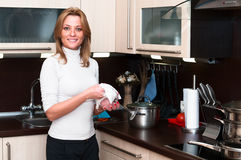 Woman in kitchen interior. Beautiful happy smiling female in kitchen interior. One person only Stock Photos