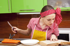 Woman in the kitchen with knife recipe book. Serious woman in the kitchen with knofe is reading recipe book Royalty Free Stock Photos
