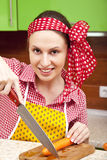 Woman in the kitchen with knife and vegetables Stock Photography