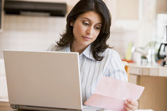 Woman in kitchen with laptop Royalty Free Stock Images