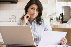 Woman in kitchen with laptop stock photo