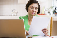Woman in kitchen with laptop and paperwork. Looking worried Stock Photo