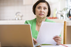 Woman in kitchen with laptop and paperwork Royalty Free Stock Photos