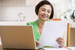Woman in kitchen with laptop and paperwork smiling Royalty Free Stock Photo