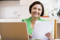 Woman in kitchen with laptop and paperwork smiling Stock Photos