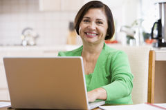 Woman in kitchen with laptop smiling Stock Image