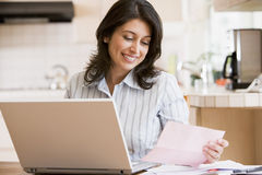 Woman in kitchen with laptop smiling Royalty Free Stock Photos