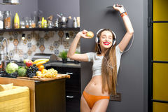 Woman in the kitchen. Lifestyle portrait of a young sports woman listening to the music with phone and headphones in the modern kitchen interior full with fruits Royalty Free Stock Images