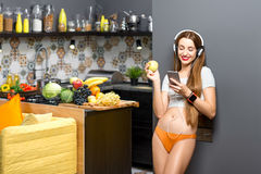 Woman in the kitchen. Lifestyle portrait of a young sports woman listening to the music with phone and headphones in the modern kitchen interior full with fruits Stock Photography