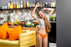 Woman in the kitchen. Lifestyle portrait of a young sports woman listening to the music with phone and headphones in the modern kitchen interior full with fruits Stock Images