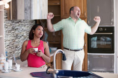 Woman in kitchen looking annoyed while man is yawning Royalty Free Stock Photos