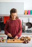 Woman in kitchen looking down while cutting mushrooms Stock Photography