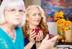 Skeptical Woman drinking coffee with friend in kitchen stock images
