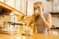 Woman in kitchen making coffee from machine Royalty Free Stock Photos