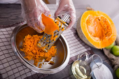 Woman in kitchen making prepares a pie with pumpkin Royalty Free Stock Images