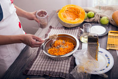 Woman in kitchen making prepares a pie with pumpkin Royalty Free Stock Photo
