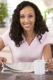 Woman in kitchen with newspaper and coffee smiling Royalty Free Stock Images