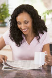 Woman in kitchen with newspaper and coffee smiling Stock Photo