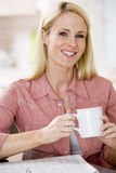 Woman in kitchen with newspaper and coffee smiling Stock Image