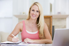 Woman in kitchen with newspaper and coffee smiling Royalty Free Stock Photos