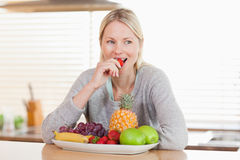 Woman in the kitchen nibbling some fruits. Woman sitting in the kitchen nibbling some fruits stock photo