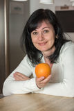 Woman in the kitchen with an orange Stock Image