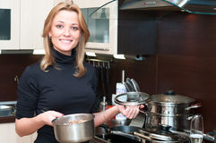 Woman in kitchen with pan Royalty Free Stock Images
