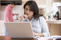 Woman in kitchen with paperwork using laptop