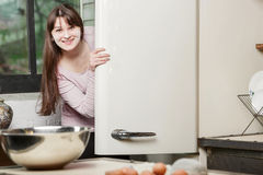 Woman in the kitchen peeking out from behind the door of an open refrigerator and smiling looking into the camera. stock photos