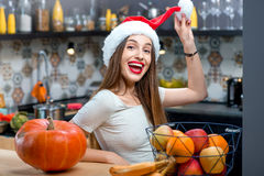 Woman in the kitchen. Portrait of a young smiling woman in the Christmas hat in the kitchen at home Stock Photo