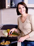 Woman is on the kitchen prepares to eat Stock Photos