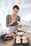 Woman in kitchen preparing cupcakes Royalty Free Stock Images
