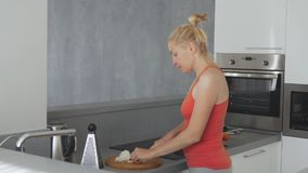 A woman in the kitchen is preparing dinner and slicing onions finely on a chopping Board. stock video footage