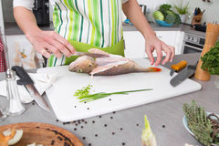 Woman in the kitchen preparing fish dinner with perch. Stock Photos