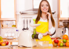 Woman in kitchen preparing fruits for juicing Stock Photography