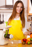 Woman in kitchen preparing fruits for juicing Stock Photos