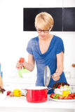 Woman in the kitchen preparing meal Royalty Free Stock Image