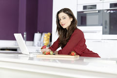 Woman in kitchen reading recipe Stock Photo